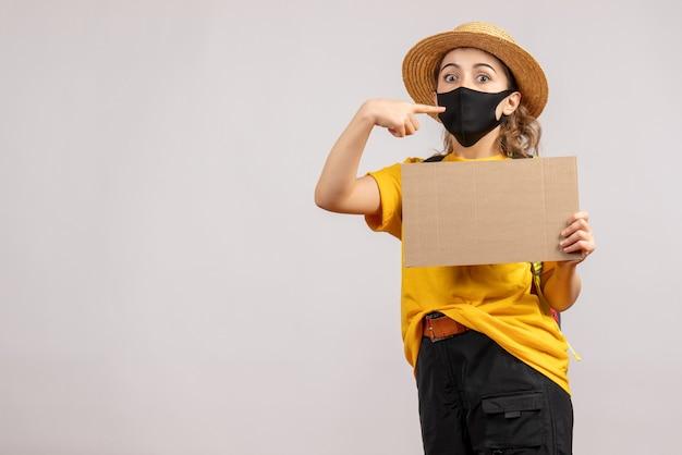 Vooraanzicht van vrouwelijke reiziger met het karton van de rugzakholding wijzende vinger haar masker op grijze muur
