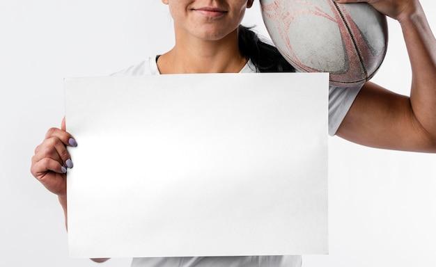 Vooraanzicht van vrouwelijke rugbyspeler die leeg aanplakbiljet en bal houdt