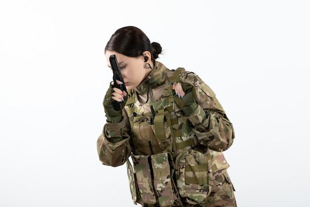 Vooraanzicht van vrouwelijke soldaat in militair uniform met pistool op witte muur