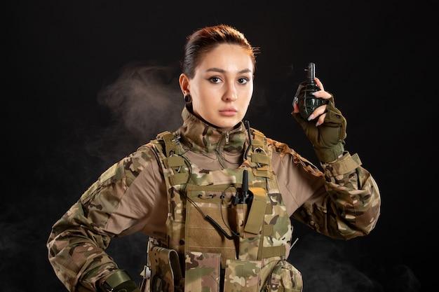 Vooraanzicht van vrouwelijke soldaat met granaat in uniform op zwarte muur