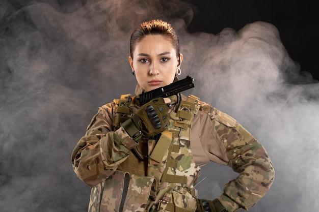 Vooraanzicht van vrouwelijke soldaat met pistool in uniform op zwarte muur
