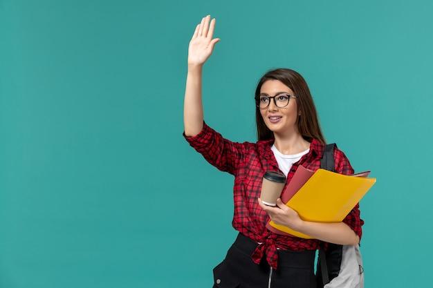 Vooraanzicht van vrouwelijke student die de dossiers en de koffie van de rugzakholding op lichtblauwe muur draagt