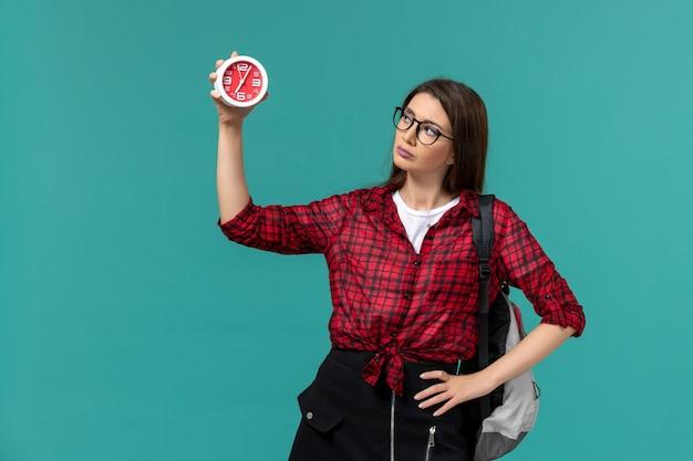 Vooraanzicht van vrouwelijke student die de klokken van de rugzakholding op de blauwe muur draagt