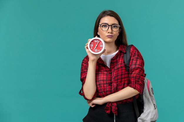 Vooraanzicht van vrouwelijke student die de klokken van de rugzakholding op de lichtblauwe muur draagt