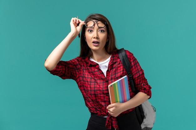 Vooraanzicht van vrouwelijke student die het voorbeeldenboek van de rugzakholding op blauwe muur draagt