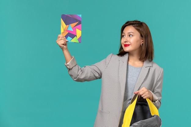 Vooraanzicht van vrouwelijke student die in grijs jasje gele rugzak en voorbeeldenboek op de lichtblauwe muur houdt