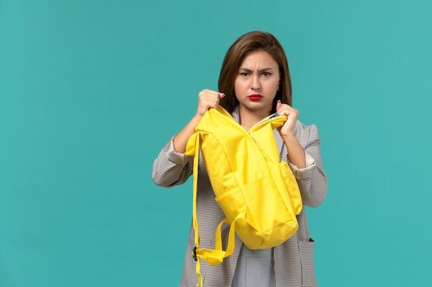 Vooraanzicht van vrouwelijke student die in grijs jasje haar gele rugzak op de lichtblauwe muur houdt