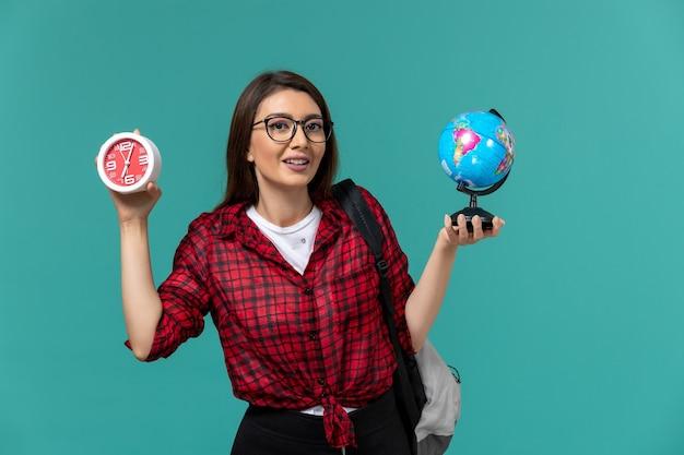 Vooraanzicht van vrouwelijke student die rugzak draagt die kleine bol en klokken op lichtblauwe muur houdt