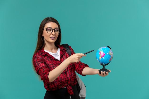 Vooraanzicht van vrouwelijke student die rugzak draagt die kleine bol en pen op lichtblauwe muur houdt