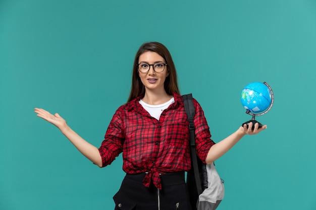 Vooraanzicht van vrouwelijke student die rugzak draagt die kleine bol op lichtblauwe muur houdt