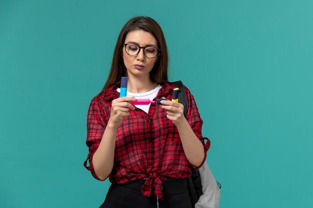 Vooraanzicht van vrouwelijke student die rugzak draagt die viltstiften op de blauwe muur houdt