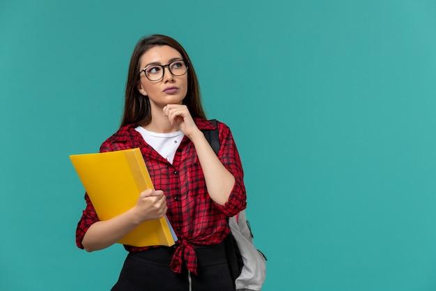 Vooraanzicht van vrouwelijke student die rugzak draagt en dossiers houdt die op lichtblauwe muur denken