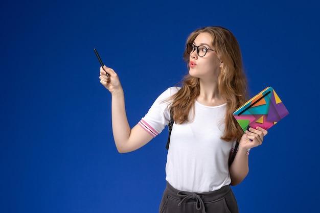 Vooraanzicht van vrouwelijke student in de witte pen en voorbeeldenboek van de overhemdsholding op de blauwe muur