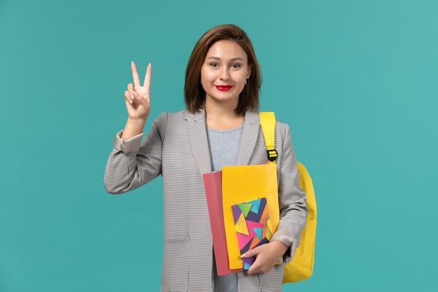 Vooraanzicht van vrouwelijke student in grijs jasje die de gele dossiers van de rugzakholding en voorbeeldenboek draagt die op de blauwe muur glimlachen