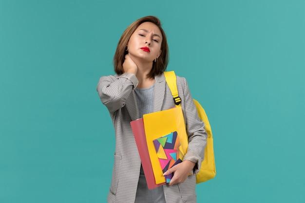 Vooraanzicht van vrouwelijke student in grijs jasje die de gele dossiers van de rugzakholding en voorbeeldenboek dragen met nekpijn op blauwe muur