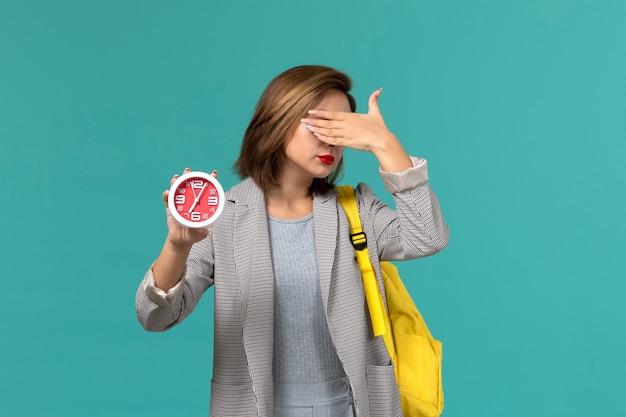 Vooraanzicht van vrouwelijke student in grijs jasje die de gele klokken van de rugzakholding draagt en haar gezicht op blauwe muur behandelt