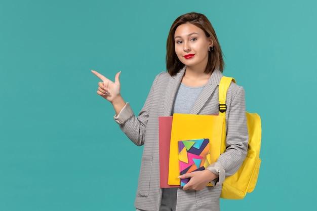 Vooraanzicht van vrouwelijke student in grijs jasje die gele rugzak draagt die dossiers en voorbeeldenboek houdt die enkel op blauwe muur glimlachen