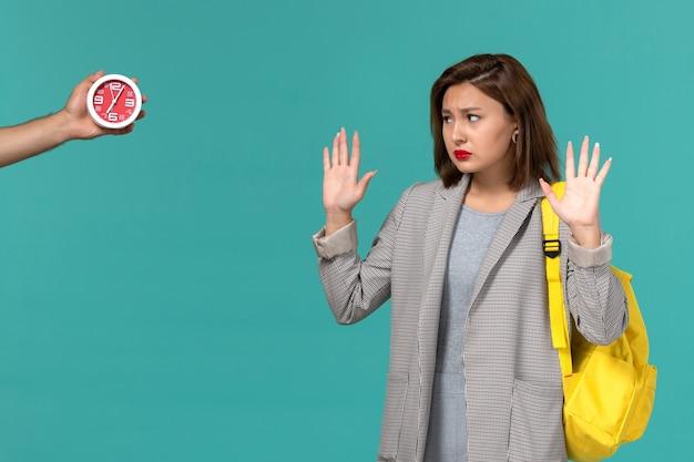 Vooraanzicht van vrouwelijke student in grijs jasje die gele rugzak draagt die klokken op de lichtblauwe muur bekijkt