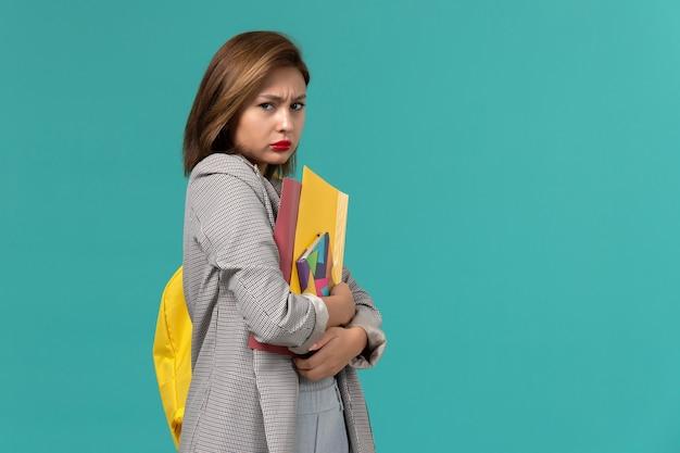Vooraanzicht van vrouwelijke student in grijs jasje die gele rugzak draagt die voorbeeldenboek en dossiers op de lichtblauwe muur houdt