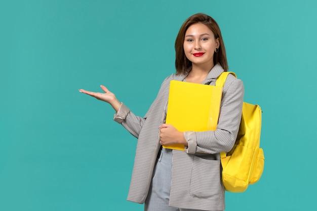 Vooraanzicht van vrouwelijke student in grijs jasje die haar gele rugzak draagt en dossiers op de lichtblauwe muur houdt