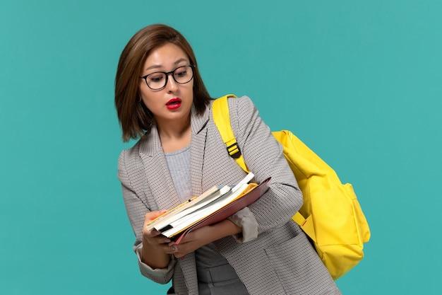 Vooraanzicht van vrouwelijke student in grijze jas gele rugzak met boeken op de blauwe muur