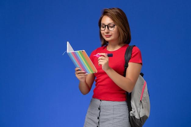 Vooraanzicht van vrouwelijke student in rood overhemd die met rugzak viltstiften houden die voorbeeldenboek op de blauwe muur lezen