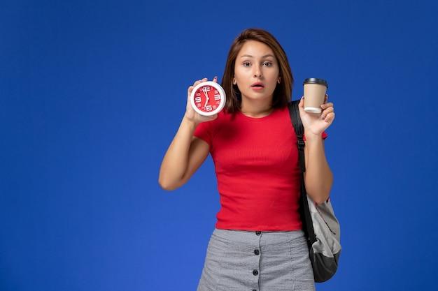 Vooraanzicht van vrouwelijke student in rood overhemd met de klokken van de rugzakholding en koffie