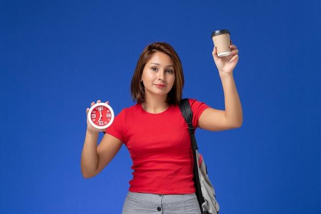 Vooraanzicht van vrouwelijke student in rood overhemd met klokken en koffie van de rugzakholding op de blauwe muur