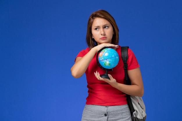 Vooraanzicht van vrouwelijke student in rood overhemd met rugzak die kleine bol op de blauwe muur houdt