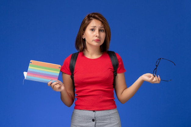 Vooraanzicht van vrouwelijke student in rood overhemd met voorbeeldenboek van de rugzakholding op de lichtblauwe muur