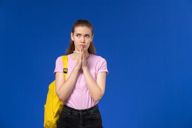Vooraanzicht van vrouwelijke student in roze t-shirt met gele rugzak die op de blauwe muur denken