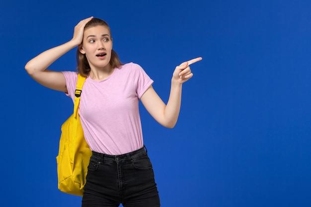 Vooraanzicht van vrouwelijke student in roze t-shirt met gele rugzak die op lichtblauwe muur wijst
