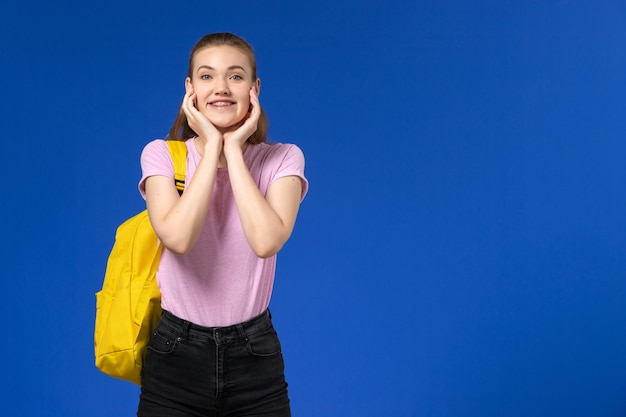 Vooraanzicht van vrouwelijke student in roze t-shirt met gele rugzak glimlachend en poseren op de blauwe muur