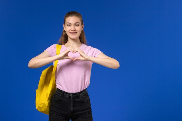 Vooraanzicht van vrouwelijke student in roze t-shirt met gele rugzak glimlachend op de blauwe muur