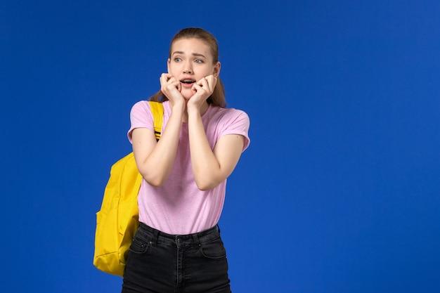Vooraanzicht van vrouwelijke student in roze t-shirt met gele rugzak met bang uitdrukking op de blauwe muur