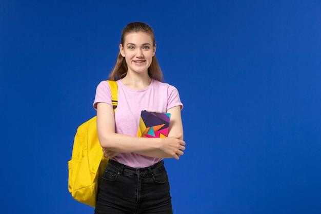 Vooraanzicht van vrouwelijke student in roze t-shirt met gele rugzak met voorbeeldenboek op de blauwe muur