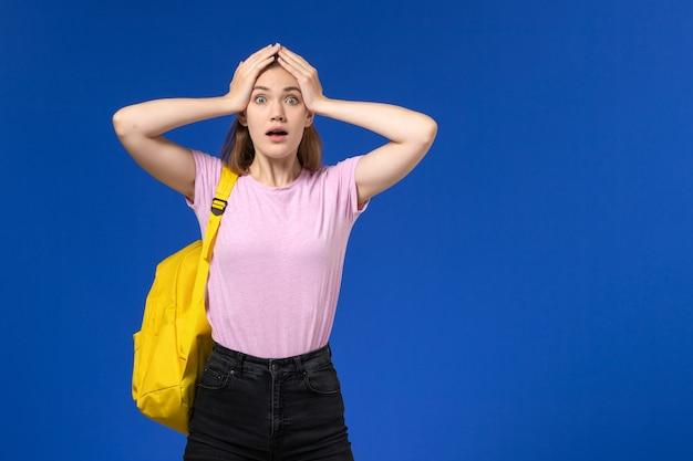 Vooraanzicht van vrouwelijke student in roze t-shirt met gele rugzak op de lichtblauwe muur