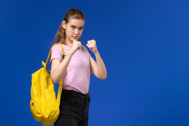 Vooraanzicht van vrouwelijke student in roze t-shirt met gele rugzak poseren in bokstribune op blauwe muur
