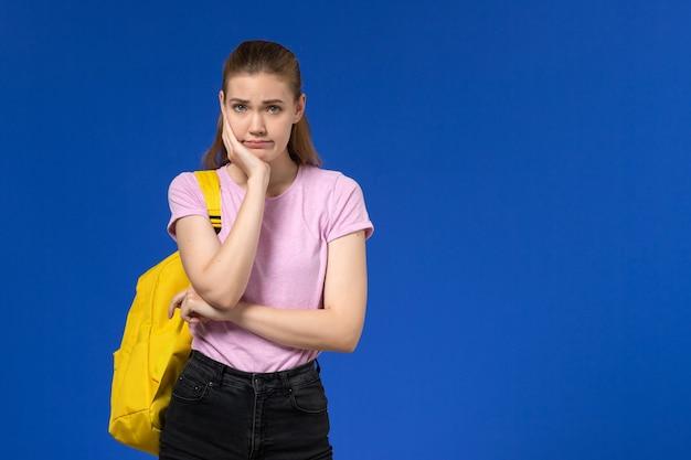 Vooraanzicht van vrouwelijke student in roze t-shirt met gele rugzak poseren met gestreste uitdrukking op de blauwe muur