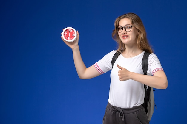 Vooraanzicht van vrouwelijke student in wit overhemd die de klokken van de rugzakholding op blauwe muur dragen