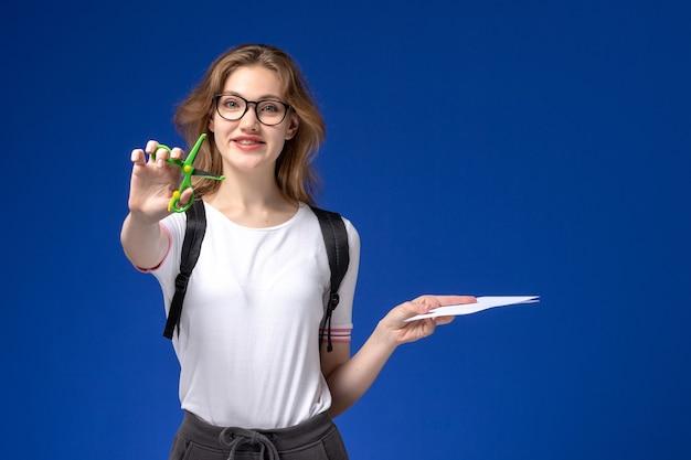 Vooraanzicht van vrouwelijke student in wit overhemd die rugzak draagt en document en schaar op de blauwe muur houdt