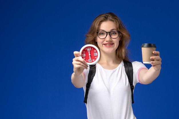 Vooraanzicht van vrouwelijke student in wit overhemd die rugzak draagt en klokken en koffie houdt die op de blauwe muur glimlachen