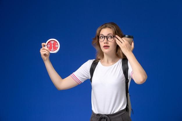 Vooraanzicht van vrouwelijke student in wit overhemd die rugzak draagt en klokken en koffie op de blauwe muur houdt