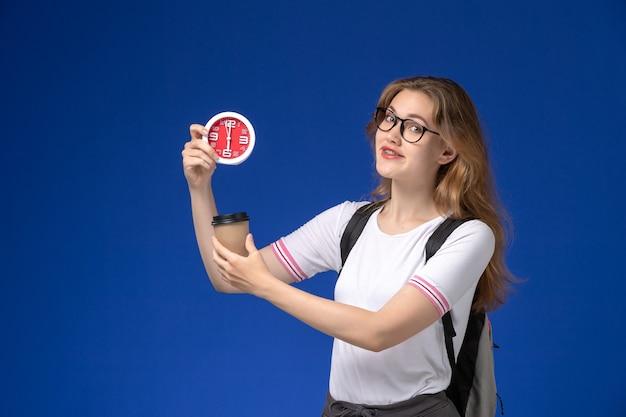 Vooraanzicht van vrouwelijke student in wit overhemd die rugzak draagt en klokken en koffie op het blauwe wijfje van de bureauhogeschool houdt
