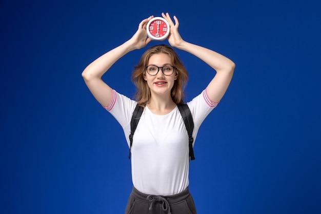 Vooraanzicht van vrouwelijke student in wit overhemd die rugzak draagt en klokken met glimlach op de blauwe muur houdt