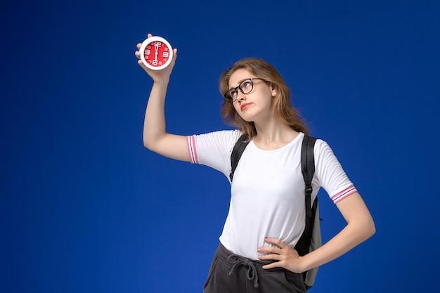 Vooraanzicht van vrouwelijke student in wit overhemd die rugzak draagt en klokken op blauw bureau houdt