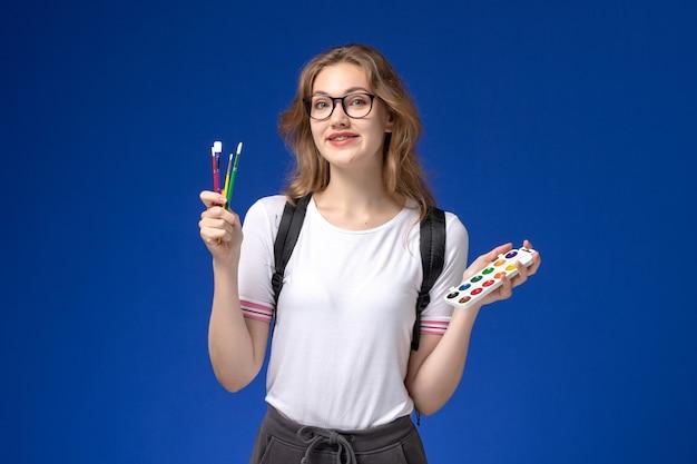 Vooraanzicht van vrouwelijke student in wit overhemd die rugzak draagt en kunstverfborstels op de blauwe muur houdt