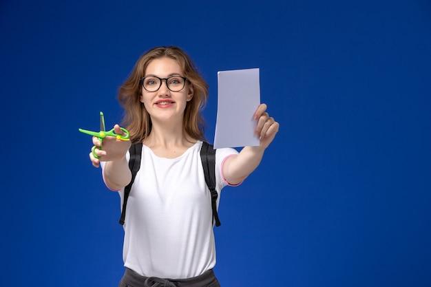Vooraanzicht van vrouwelijke student in wit overhemd die rugzak draagt en papier en schaar houdt