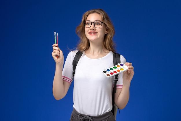 Vooraanzicht van vrouwelijke student in wit overhemd die rugzak draagt en verf en borstels houdt