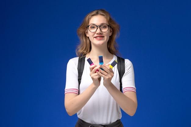 Vooraanzicht van vrouwelijke student in wit overhemd die rugzak draagt en viltstiften op de blauwe muur houdt